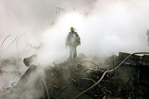 A fireman walks amongst the rubble and the smo...