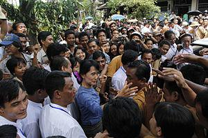 English: Aung San Suu Kyi greeting supporters ...