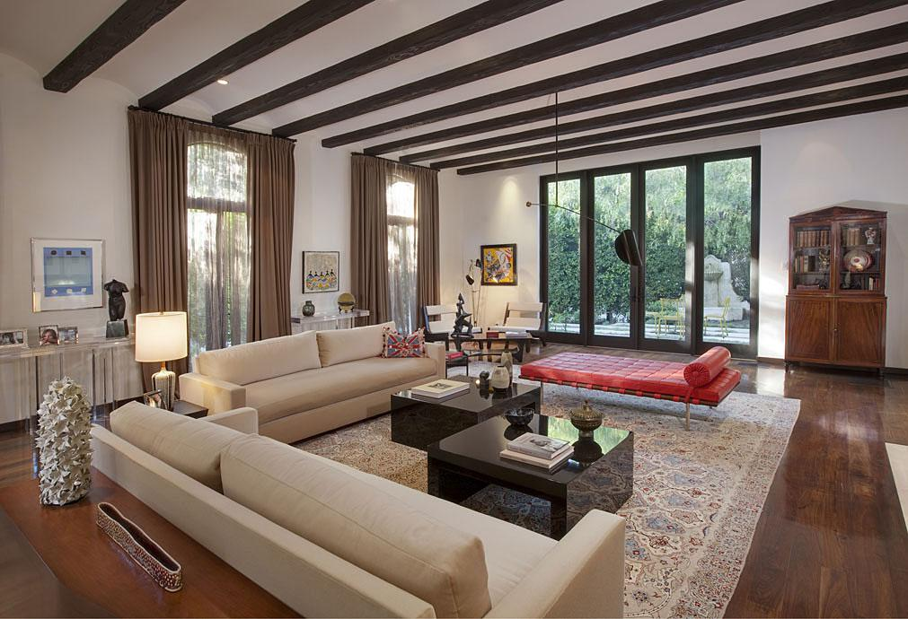 Living room features beautiful wood floors and exposed wood beam ceilings