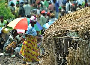 A displaced Congolese woman stands in her rams...